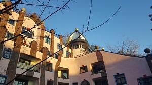 Teilansicht der Grünen Zitadelle in Magdeburg, samt rosa Putz an den Wänden, Türmchen und immer unterschiedlich geformten Fenstern.