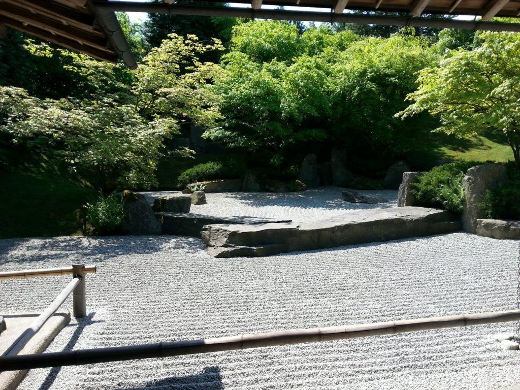 Ein Steingarten mit Bäumen und Sträuchern im Hindergrund.