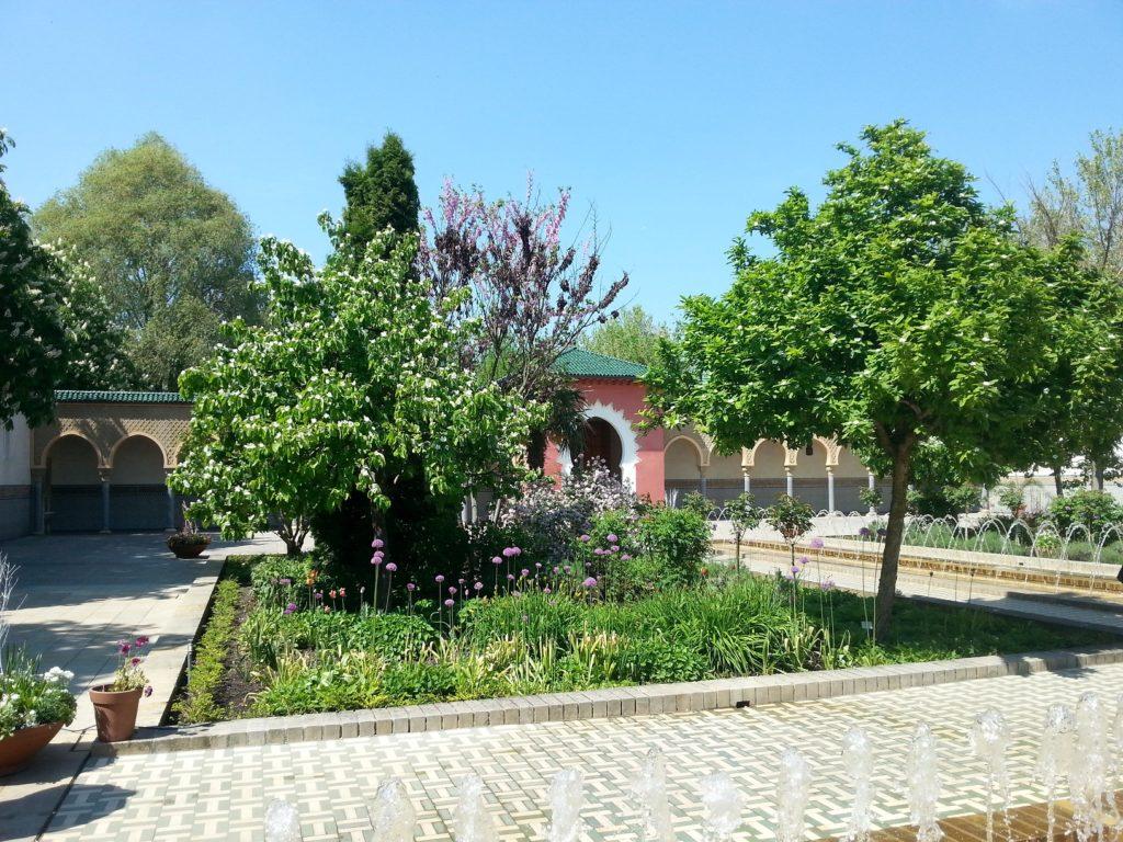 Gefliester Innenhof mit Wasserspiel und Gartenflächen
