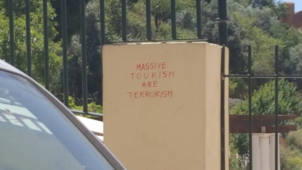 """Stein mit der Inschrift """"Massive Tourism are Terrorism"""""""