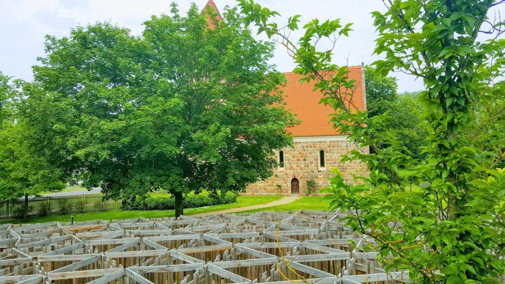 Blick vom Irrgarten aus auf Bäume und die steinerne Dorfkirche.