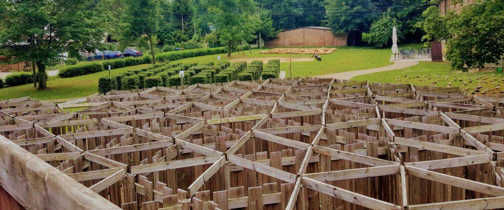 Blick vom Irrgarten über dessen Gänge und hin zu einem Hecken- und Bodenlabyrinth.
