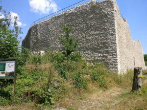 Meterhohe Burgmauer mit Geländer.
