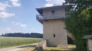Rekonstruierter Wehrturm aus Stein mit einem umlaufenden Holzgeländer und flachem Dach an einem Feld.