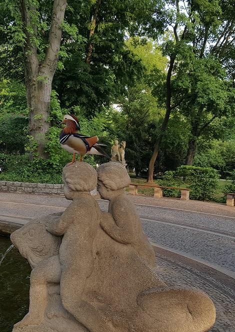 Zwei Kinderfiguren, die auf einem Fisch sitzen und auf dem Kopf der einen Figur sitzt eine Mandarinente.