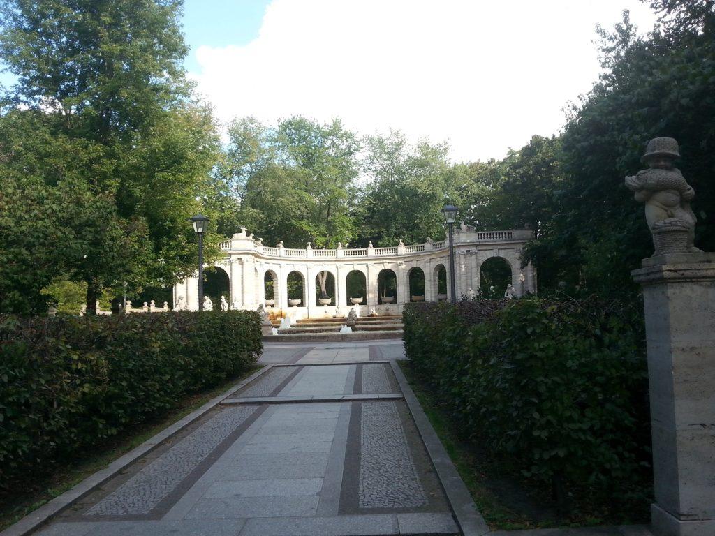 Eingangsbereich zum Märchenbrunnen: gepflasterter Weg mit Blick auf den Brunnen und einen ihn abschließenden Bogen.