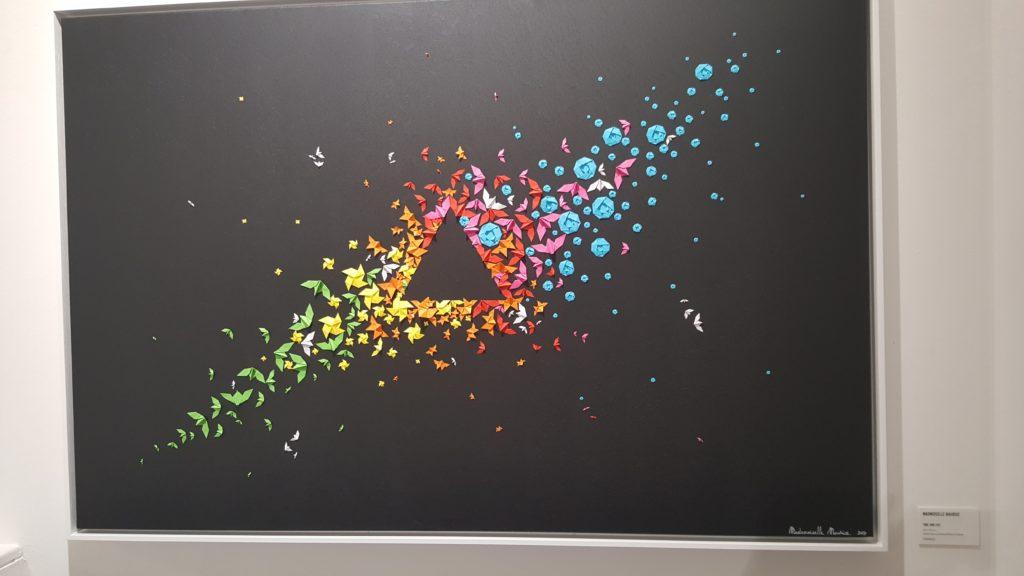 Viele kleine gefaltete Kraniche und Blumen in unterschiedlichen Farben die ein Dreieck umrahmen.