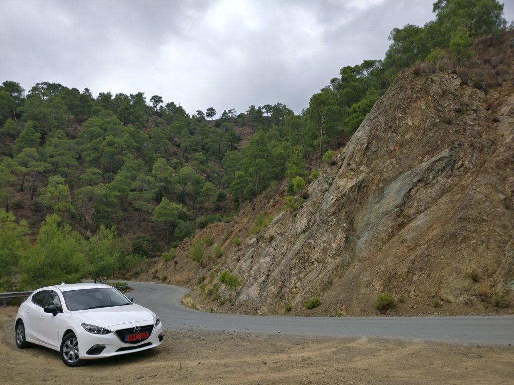 Blick auf ein weißes Auto in einer Haltebucht einer Serpentine. Im Hintergrund sind ein Berg und Bäume.