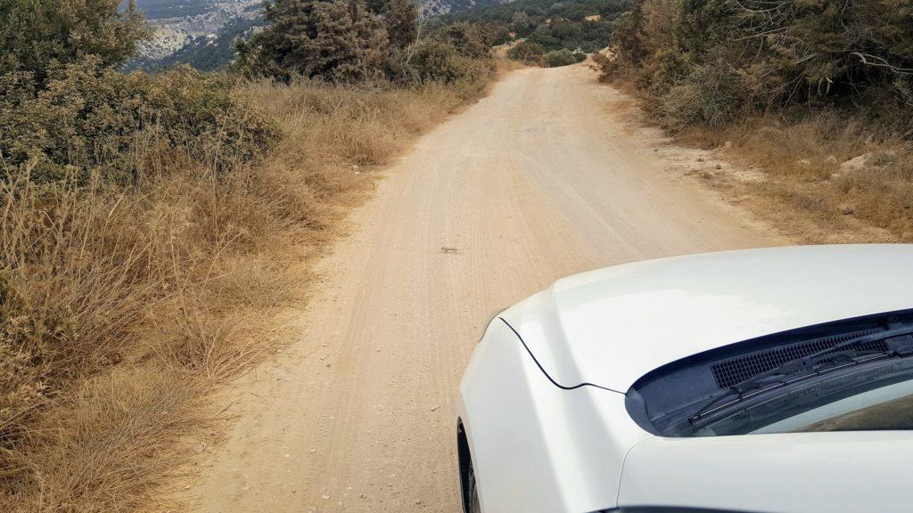 Blick aus dem Auto auf eine Sandstraße.