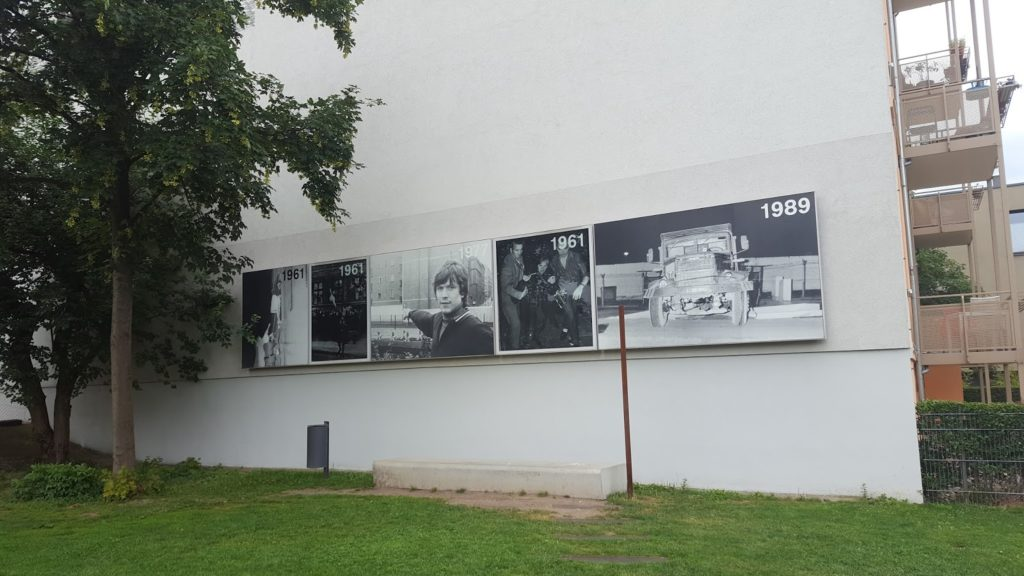 Fotos an einer Hauswand, die das Areal von 1961 bis 1989 zeigen.