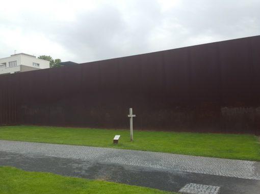 Ein weißes Gedenkkreuz auf grünem Gras vor einer rostbraunen Wand.