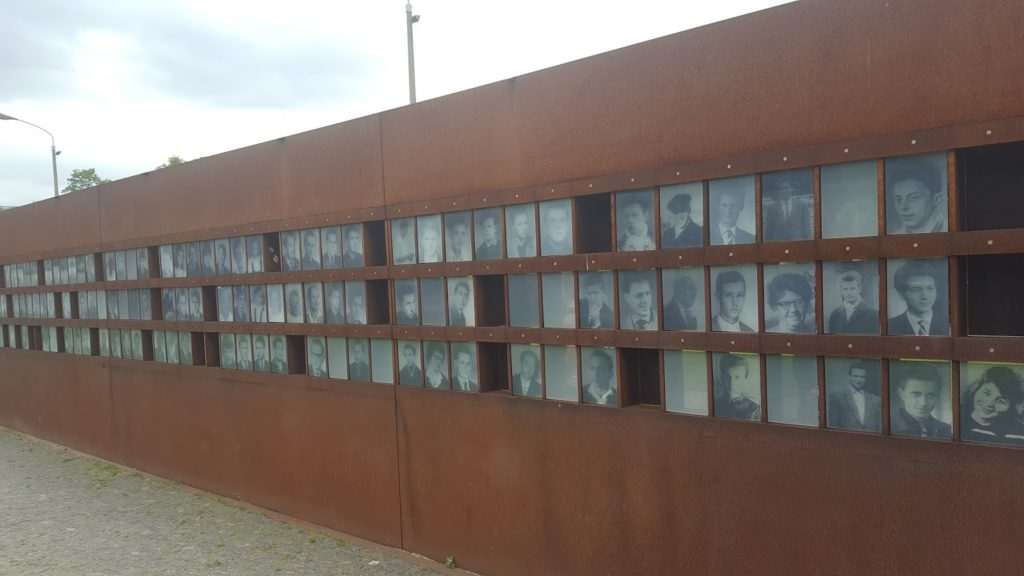 Rostfarbenen Metallwand mit einzelnen Feldern auf denen Porträts zu sehen sind.