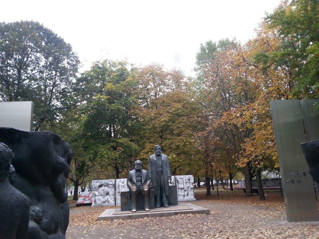 Blick auf die Marx-Engels-Figuren. Marx sitzend, Engels stehend, umgeben von Metallstelen und Steinreliefs.