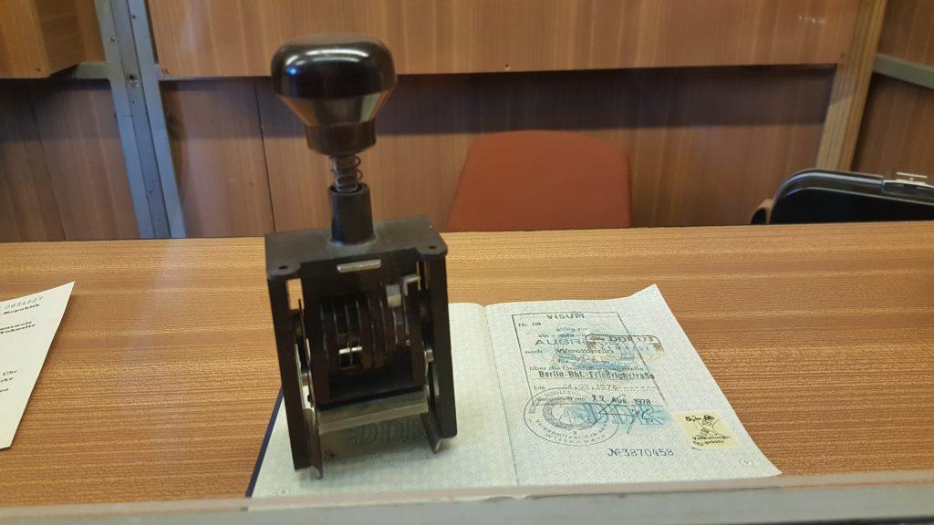 Blick auf den Tisch einer Kontrollkabine auf dem sich ein aufgeschlagener Pass und Stempel befinden.