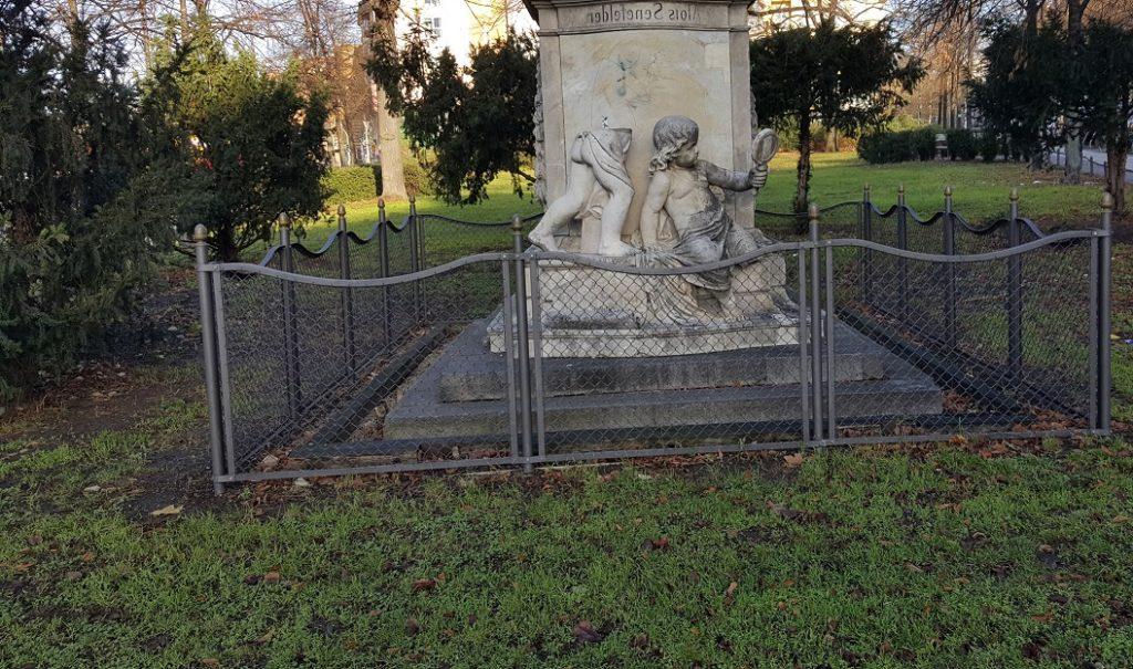 Der untere Teil des Senefelder-Denkmals mit einer Figur, das einen Spiegel in der Hand hält.