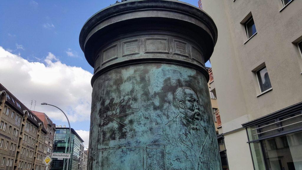 Bronzene Litfaßsäule mit dem Gesicht von Litfaß.