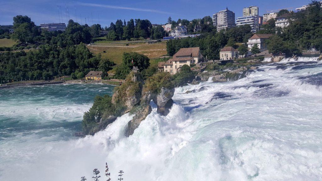 Rheinfallfelsen inmitten des Wasserfalls umspült von weißem, rauschenden Wasser.