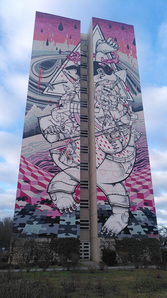 Mural On Tiptoes: Puzzleteile, rosa-schwarz-graue Farbgebung und eine Figur, die auf Zehen steht.