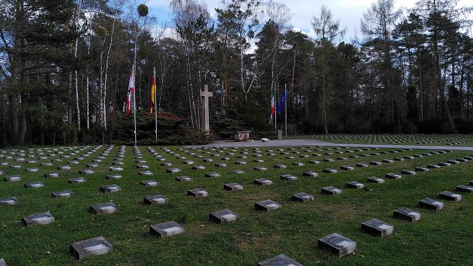 Wiese mit Grabplatten und im Hintergrund ein Kreuz und italienische, deutsche und europäische Fahnen.