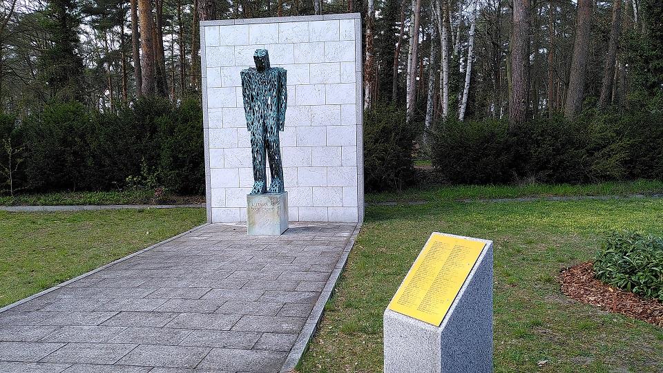 Metallskulptur mit Patina, die wie ein Mensch mit geneigtem Kopf aussieht.
