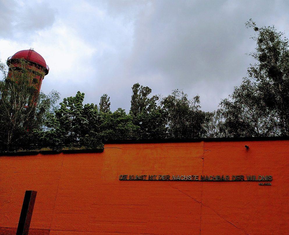 Eingangsbereich des Wasserturms mit orange-farbener Wand und einem Zitat zur Harmonie von Wildnis und Kunst in Metalllettern.