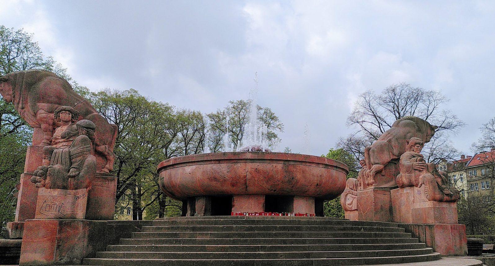 Der rote Stierbrunnen mit Brunnenschale und zwei Stierfiguren in der Frontalansicht.