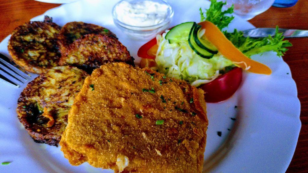 Panierter Käse, runde, dunkle Kartoffelpuffer, etwas Salatdekoration mit Krautsalat und ein Schälchen Tartarsoße.