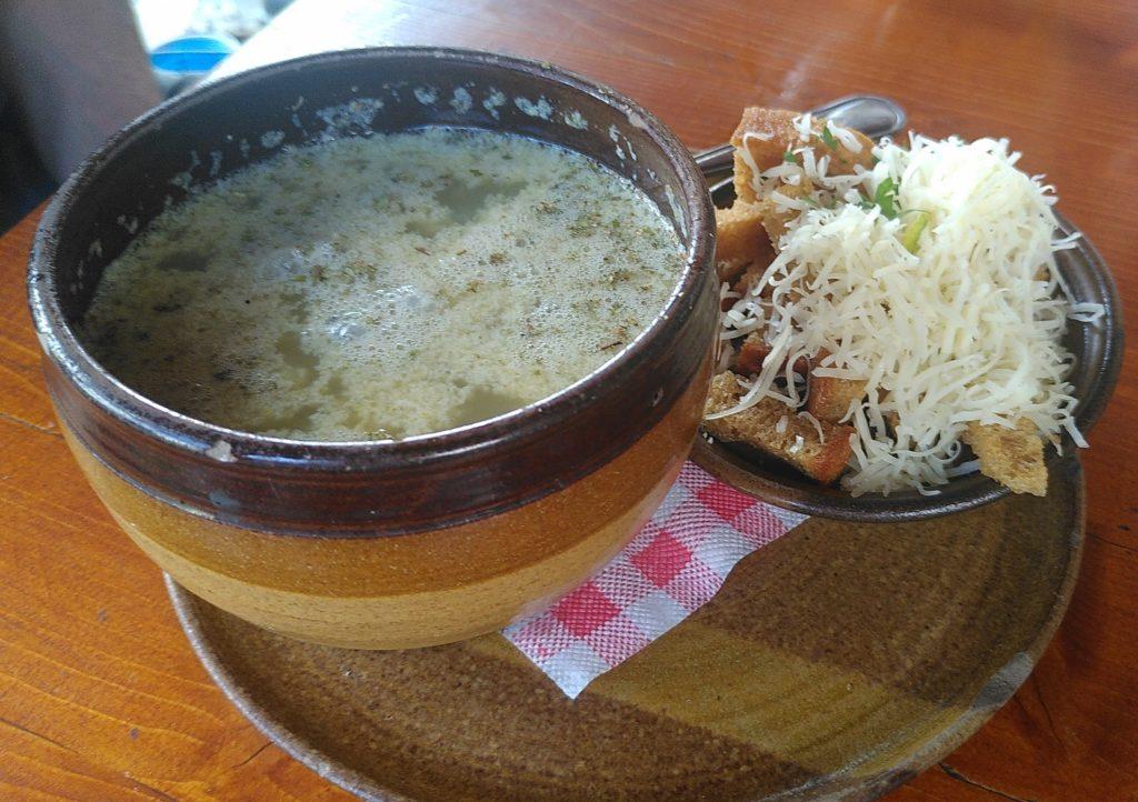 Eine Schüssel Knoblauchsuppe mit einer Schale geröstetem Brot und Käse.