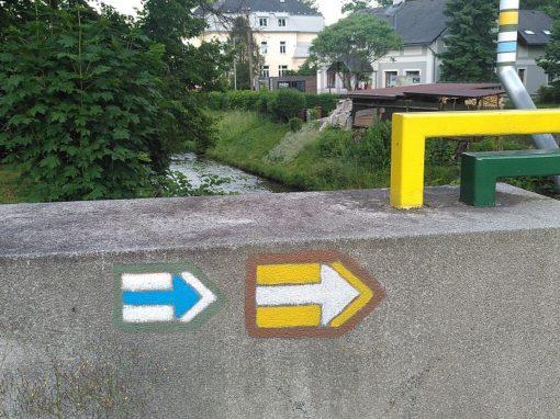 Betonmauer auf der sich zwei gemalte Pfeile befinden.