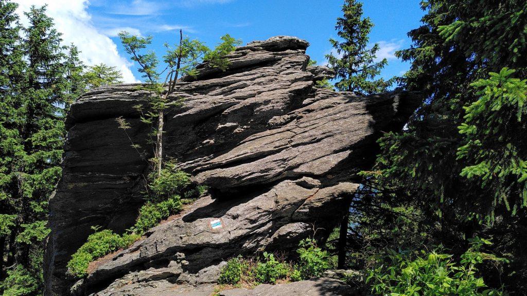 Einzelner grauer riesiger Stein mit Wanderwegmarkierung.